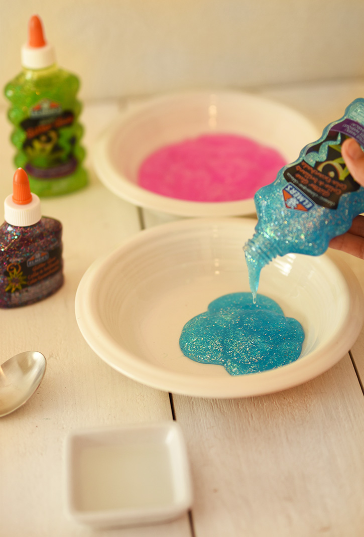 How To Make Rainbow Slime - Pour Blue Elmers Glitter Glue Into A Bowl - Cool and Easy Crafts for Kids and Teens - Ingredients and Step by Step Tutorial for Making Slime At Home - Cheap DIY Projects for Teens and Teenagers - Girls and Boys Love Making Slime