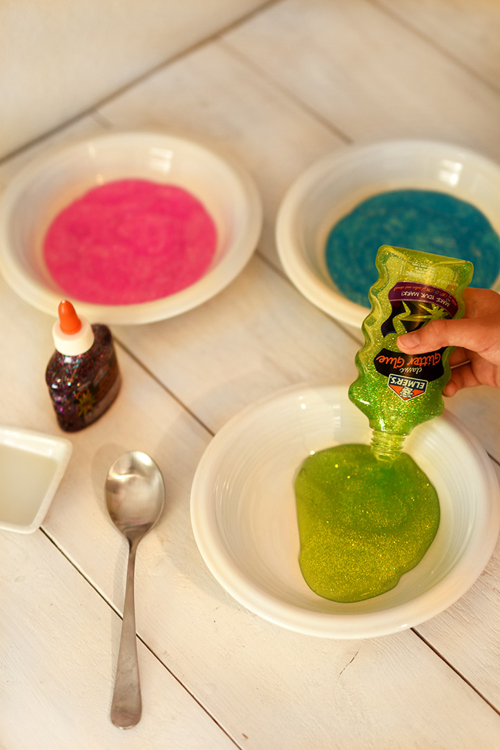 How To Make Rainbow Slime - Pour Green Elmers Glitter Glue Into A Bowl - Cool and Easy Crafts for Kids and Teens - Ingredients and Step by Step Tutorial for Making Slime At Home - Cheap DIY Projects for Teens and Teenagers - Girls and Boys Love Making Slime